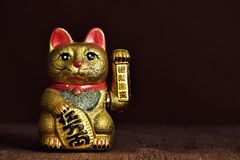 Chinese lucky cat. A golden chinese lucky cat with its left paw raised, on a rustic wooden surface stock photography