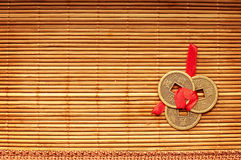 Chinese lucky coins. Three Chinese lucky coins tied with red ribbon on wooden mat stock image