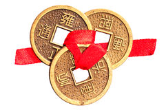 Chinese lucky coins on white. Three chinese lucky coins on yang side tied with red ribbon, isolated on white background. Symbol of wealth in feng-shui royalty free stock photography