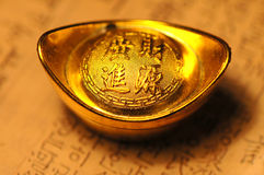 Chinese lucky gold ingot on calligraphy backgr Stock Photos