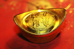 Chinese lucky gold ingot on red calligraphy backgr Royalty Free Stock Images