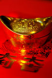 Chinese lucky gold ingot on red calligraphy backgr Royalty Free Stock Photo