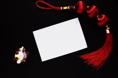Chinese lucky knot, maneki neko cat figurine and empty paper card on black. Chinese New Year decor. White paper card. Chinese Lunar New Year top view photo stock photo