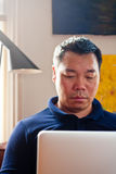 Chinese male on laptop Royalty Free Stock Photography