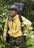 Chinese Man Backpacking Through Jungle. A Chinese man hikes through the thick jungle terrain with his large backpack in Yunnan province, China Stock Photo