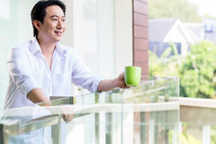 Chinese man on balcony of home with coffee Stock Photography