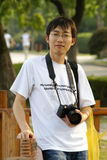 Chinese man with camera. Half body portrait of Chinese man with digital camera around neck Stock Photo
