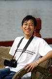 Chinese man with camera. Happy Chinese man with digital camera, water in background Stock Image