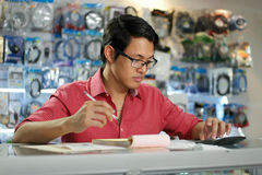 Chinese Man In Computer Shop Checking Bills And Invoices Royalty Free Stock Photo