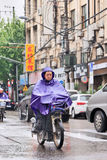 Chinese man dressed in rainwear on an e-bike. Shanghai, China. SHANGHAI–MAY 4, 2014. Chinese man dressed in rainwear on an e-bike. Shanghai has a humid royalty free stock images