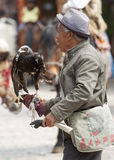 Chinese Man with Eagle. A Chinese man holds an eagle in the central square of Old Town Lijiang, selling photos with the bird Stock Image