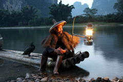 Chinese man fishing with cormorants birds in Royalty Free Stock Photography