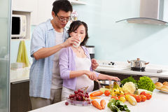 Chinese man giving milk to her pregnant wife Stock Photo