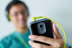 Chinese Man With Green Headphones Listens Music Podcast Phone. Chinese man watching podcast on mobile phone, listening with green big earphones. Copy space and Stock Images