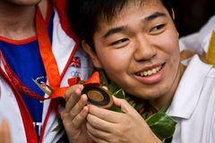Chinese man holds Olympic medal. Chinese fan holds Tony Jeffries Olympic bronze medal. Great Brittan�s men�s light heavyweight boxer. Beijing, China 2008 Royalty Free Stock Photo