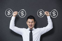 Chinese man lifting dumb bell weights with dollar sign on them. Stock Image