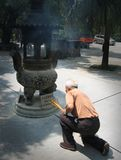 Chinese man lighting insence. At a Hongkong temple Royalty Free Stock Photos