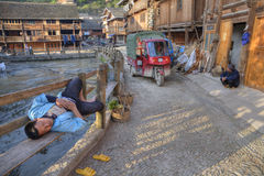 Chinese man lying on bench midst of village street, China. royalty free stock photography