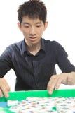 Chinese man play Mahjong Stock Image