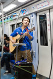 Chinese man playing a guitar and singing for money Stock Image