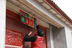 Chinese man post new year`s scrolls , Spring festival couplets and Mars at red door in China Stock Image