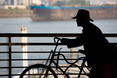 Chinese Man pushing his bicycle with the river and a boat in the Royalty Free Stock Image