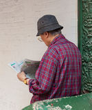 A Chinese man reading the newspaper at Chinatown. NEW YORK CITY, USA - JULY 07, 2015: A Chinese man, leaning against a wall reading the newspaper at Chinatown stock photo