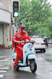 Chinese man in red rainwear on a retro style scooter, Shanghai, China Stock Images