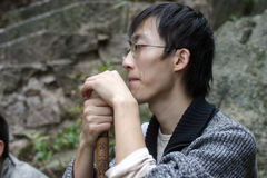 Chinese man resting. A young bespectacled Chinese man holding an Alpine stick and sitting resting while on the way up a mountain Royalty Free Stock Photo