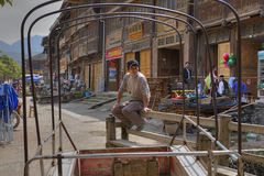 Chinese man resting on bench of rural shopping street, China. Stock Images