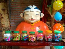 Chinese man is selling candies. Chinese man statue in Thai grocery. It's a colorful and cute photo Stock Photos