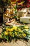 Chinese man sells bouquets of fresh flowers on the street of Bugis, Singapore royalty free stock photography