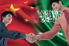 Chinese man shaking hands with Arabian person Royalty Free Stock Image
