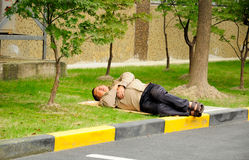 Chinese man sleeping outside Stock Image
