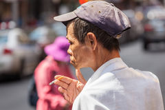 Chinese man smokes a cigarette in Chinatown in Manhattan. Stock Image
