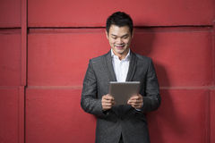 Chinese man with a tablet computer. Royalty Free Stock Photos