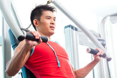 Chinese Man training strength in fitness gym Stock Photo