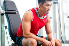 Chinese Man training strength in fitness gym Royalty Free Stock Images