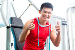Chinese Man training strength in fitness gym Royalty Free Stock Photo