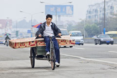 Chinese man transports a mattress. GUANGZHOU-FEB. 22, 2012. Chinese man transports a mattress with a freight tricycle on Feb. 22, 2012 in Guangzhou. Cargo bikes Royalty Free Stock Images