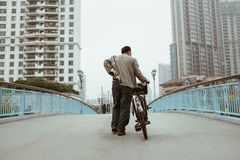 Chinese man walking with bike in Shanghai, China Stock Photo