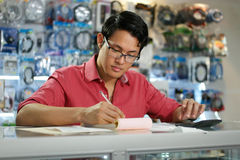 Chinese Man Working In Computer Shop Checking Bills And Taxes Royalty Free Stock Photography