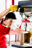 Chinese man working with drill in factory Stock Photos