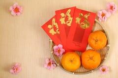 3 Chinese mandarijnen in mand met Chinese Nieuwjaar rode pakketten - Reeks 3 Royalty-vrije Stock Foto