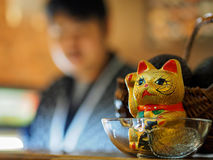 Chinese maneki cat with chef in background. Chinese maneki cat in restaurant with chef in background Stock Photos