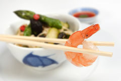 Chinese meal. Oriental vegetables with prawn on chopsticks Stock Photo