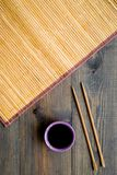 Chinese meal concept. soy sauce in bowl near chopsticks and bamboo table mat on dark wooden background top view pattern royalty free stock photography