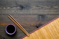 Chinese meal concept. soy sauce in bowl near chopsticks and bamboo table mat on dark wooden background top view copy stock photos