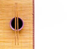 Chinese meal concept. soy sauce in bowl near chopsticks and bamboo table mat on white background top view copy space stock photos