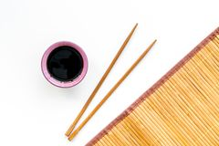 Chinese meal concept. soy sauce in bowl near chopsticks and bamboo table mat on white background top view pattern stock image